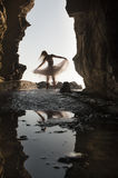 Young beautiful bride couple dancing in rock archway with skirt. At beach Royalty Free Stock Image