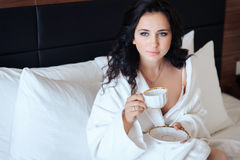 Young beautiful bride with a cup of coffee waiting for her groom Royalty Free Stock Photography