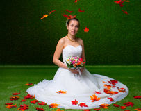 Young and beautiful bride with the flower bouquet  and red maple leaf Royalty Free Stock Photo