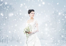 Young and beautiful bride with a flower bouquet on the snow Royalty Free Stock Photos