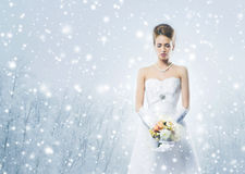 Young and beautiful bride with the flower bouquet on the snow Royalty Free Stock Photo