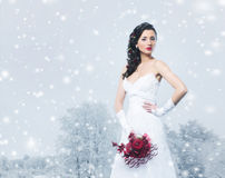 Young and beautiful bride with a flower bouquet on the snow royalty free stock photo