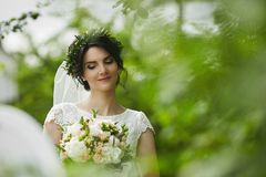 Young beautiful bride with green floral wreath in her wedding hairstyle enjoys a bouquet of rose flowers outdoors in royalty free stock photos