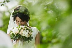 Young beautiful bride with green floral wreath in her wedding hairstyle enjoys a bouquet of rose flowers outdoors in royalty free stock photo
