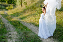 Young beautiful bride on green lawn passage Royalty Free Stock Photos
