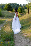 Young beautiful bride on green lawn passage Royalty Free Stock Photography