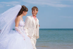 Young and beautiful bride and groom on the beach Stock Images