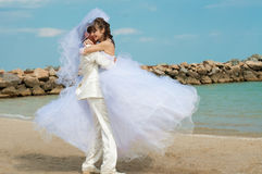 Young and beautiful bride and groom on the beach Royalty Free Stock Image