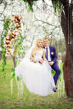 Young and beautiful bride and groom sitting on a white swing in Stock Photo