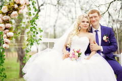 Young and beautiful bride and groom sitting on a white swing in Royalty Free Stock Photos