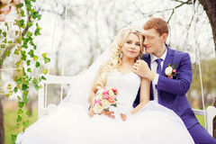 Young and beautiful bride and groom sitting on a white swing in Royalty Free Stock Photo