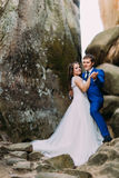 Young and beautiful bride with her elegant groom dancing in weathered rock cleft Royalty Free Stock Image