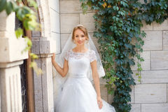 Young beautiful bride on her wedding day. Bride in white dress posing in the photo Stock Photo