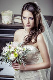 Young beautiful bride holding bouquet of flowers. Royalty Free Stock Photo