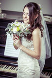 Young beautiful bride holding bouquet of flowers. Stock Photo