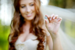 Young beautiful bride holding lucky coin Royalty Free Stock Photography