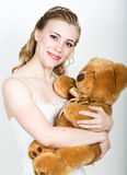 Young beautiful bride holding a teddy bear, they gently hug Royalty Free Stock Photography