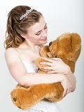 Young beautiful bride holding a teddy bear, they gently hug Royalty Free Stock Image