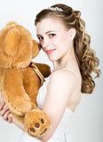 Young beautiful bride holding a teddy bear, they gently hug Royalty Free Stock Photos
