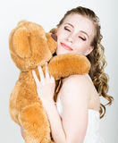 Young beautiful bride holding a teddy bear, they gently hug Stock Photo