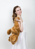 Young beautiful bride holding a teddy bear, they gently hug.  Stock Photography