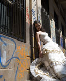Young beautiful bride leaning against spray painted building Stock Photography