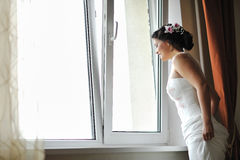 Young beautiful bride looking out the window while smiling Stock Photos