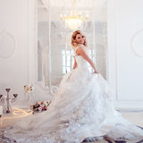 Young beautiful bride in luxurious wedding dress. Huge puffy skirt with train. Luxury light interior Royalty Free Stock Images