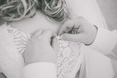 Young beautiful bride and male hands buttoning wedding dress Stock Image