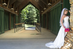 Young Beautiful Bride near barn Royalty Free Stock Image