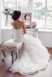 Young beautiful bride preparation at home. Wedding preparation. Beautiful young bride in white wedding dress indoors. Luxuty model looking at mirror sitting on Stock Photo