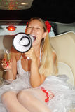Young bride sits in car, shouts into megaphone. Young beautiful bride sits in car, holds glass of champagne and shouts into megaphone. Pink wedding. Focus on stock photo