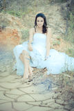 Young beautiful bride sitting in desert Royalty Free Stock Photography
