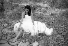 Young beautiful bride sitting in desert Stock Images