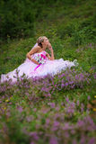 Young beautiful bride sitting at a forest glade Royalty Free Stock Photo