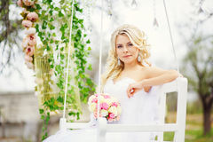 Young and beautiful bride sitting on a white swing in a spring g Stock Images