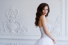Young beautiful bride standing in antique interior ornamental design done with a moldings. Luxury interior. Royalty Free Stock Images