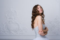 Young beautiful bride standing in antique interior ornamental design done with a moldings. Studio shot Stock Photos
