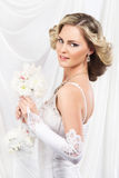Young and beautiful bride standing with a flower bouquet Royalty Free Stock Image