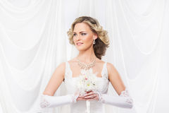 Young and beautiful bride standing with a flower bouquet Stock Photo