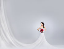 Young and beautiful bride standing with a flower bouquet. Young and beautiful bride standing with the flower bouquet over the grey background. There is a blank Stock Image