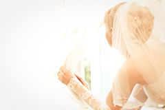Young beautiful bride waits for groom. Near the window Royalty Free Stock Image