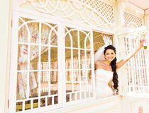 Young beautiful bride waits for groom near the window. Beautiful Bride lit by sunlight. beautiful young bride  waiting Royalty Free Stock Photos