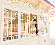 Young beautiful bride waits for groom near the window. Beautiful Bride lit by sunlight. beautiful young bride  waiting Royalty Free Stock Images