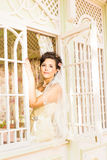 Young beautiful bride waits for groom near the window. Beautiful Bride lit by sunlight. beautiful young bride  waiting Stock Image