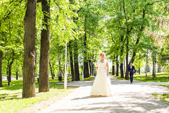 Young beautiful bride waits for groom in the spring park Stock Images