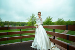 Young beautiful bride in wedding dress posing outdoors Royalty Free Stock Photo