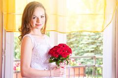 Young beautiful bride in wedding dress with red rose bouquet. Stock Photo