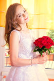 Young beautiful bride in wedding dress with red rose bouquet. Marriage and wedding concept image Stock Photography