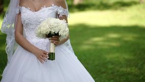 Young beautiful bride in wedding white dress with bouquet of white roses staying in a park at summer day. Young beautiful bride in wedding white dress with stock footage